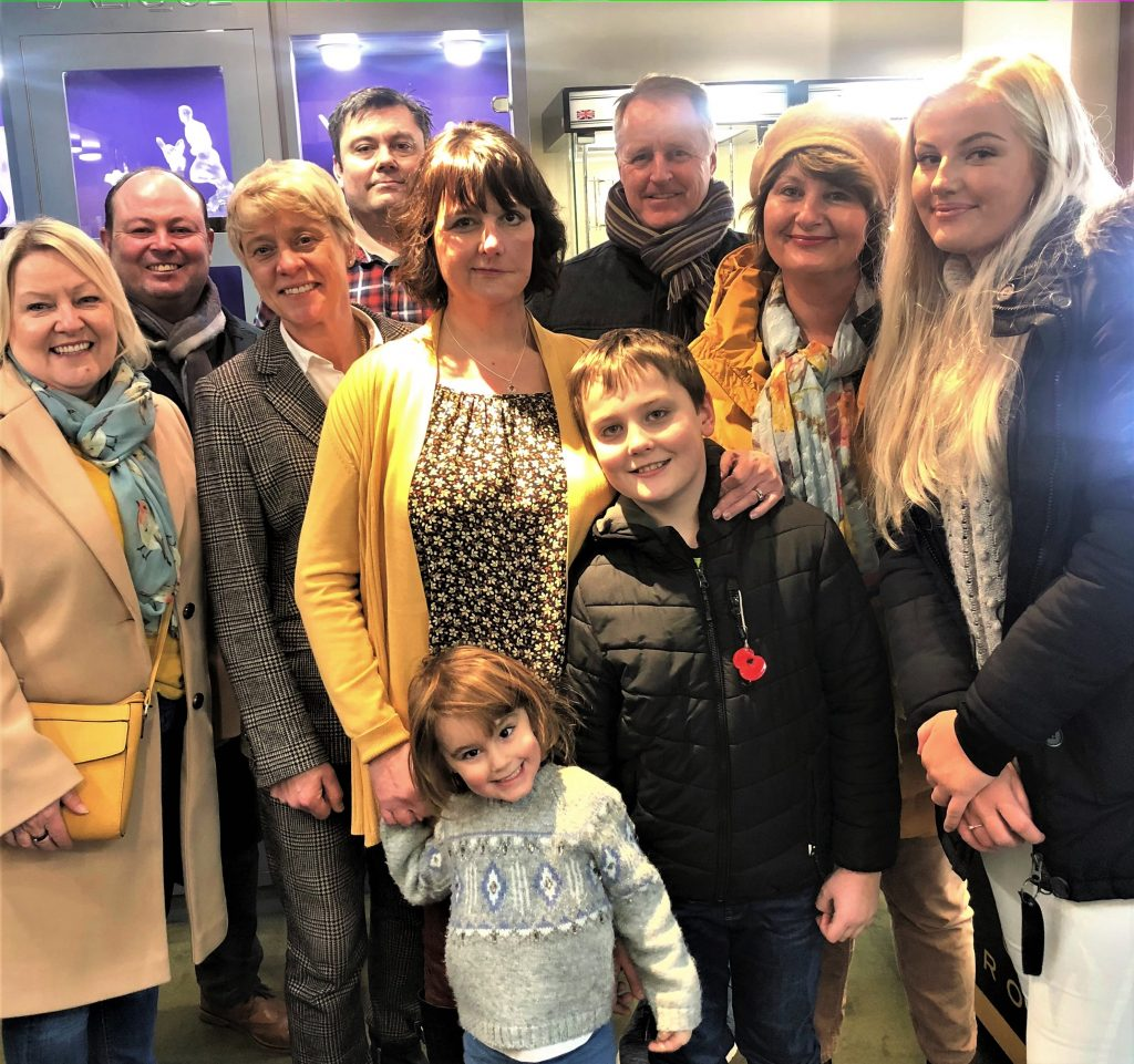 Nicky wearing the daisy charm with family and friends who nominated her