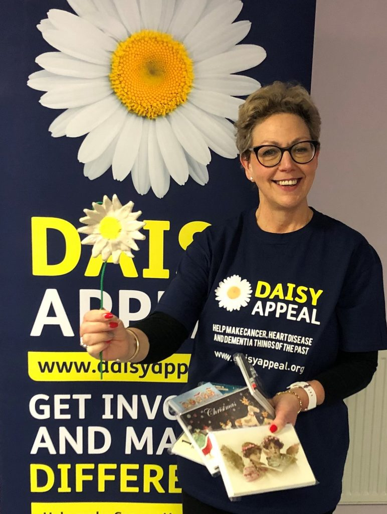 Claire Levy, Fundraiser at the Daisy Appeal, with some of the Christmas cards and one of the ceramic daisies.